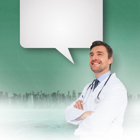 Handsome young doctor with arms crossed with speech bubble against cityscape on the horizon photo