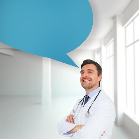 Handsome young doctor with arms crossed with speech bubble against white room with windows photo