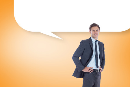 Smiling businessman with hands on hips with speech bubble against orange vignette photo