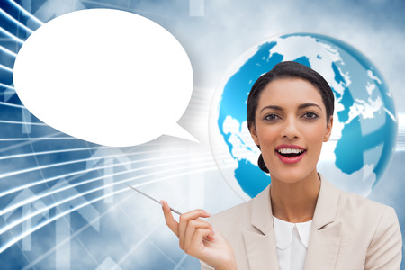 Smiling businesswoman holding a pen with speech bubble against global business graphic in blue photo