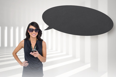 Happy brunette holding smartphone with speech bubble against curved white room photo