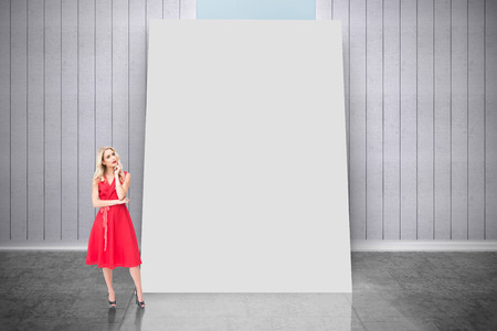 Composite image of thoughtful blonde wearing red dress against white card photo