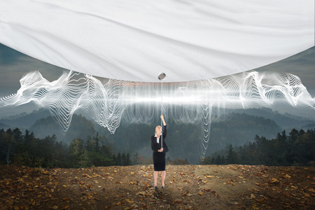 Businesswoman pulling a white screen against energy design over landscape photo