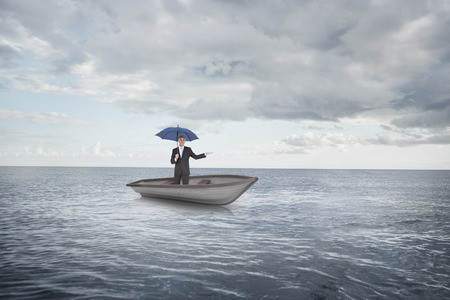 Composite image of peaceful businessman holding blue umbrella in a sailboat against cloudy sky and ocean photo