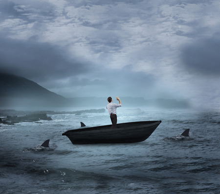 Composite image of businessman posing with arms up in a sailboat being circled by sharks photo