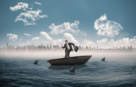 Happy businessman in a hury against sharks circling a small boat in the sea photo
