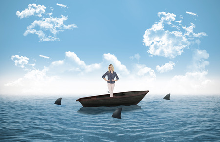 Thoughtful gorgeous blonde wearing classy clothes posing against sharks circling small boat in the ocean photo