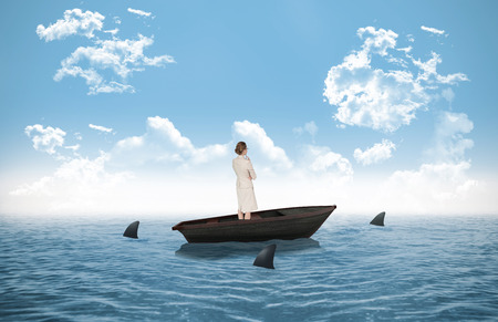 circling: Thinking businesswoman against sharks circling small boat in the ocean Stock Photo