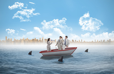 circling: Businesswoman with megaphone yelling at colleagues against sharks circling a small boat in the sea