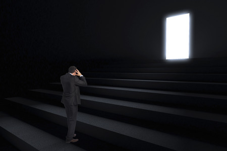 Stressed businessman with hands on head against steps leading to light in the darkness