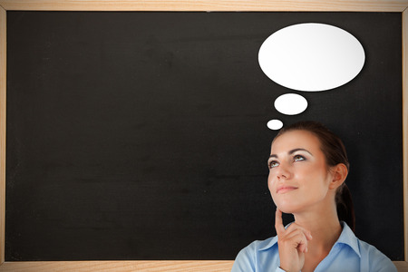 Thinking businesswoman looking upwards against chalkboard with wooden frame photo