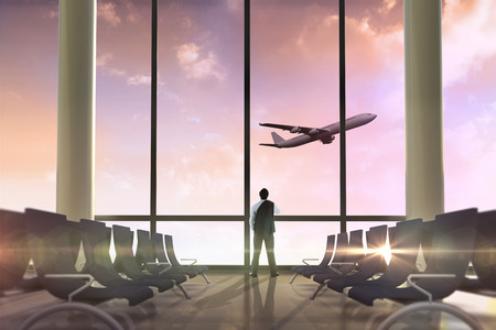 Businessman holding his jacket against airplane flying past departures lounge photo