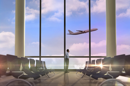Serious businessman with hand on hip against airplane flying past departures lounge photo