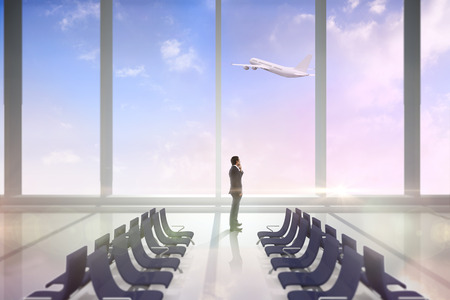Thinking businessman against airport departure area photo