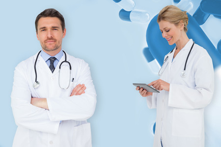 Blonde doctor using tablet pc against blue medical background with pills photo
