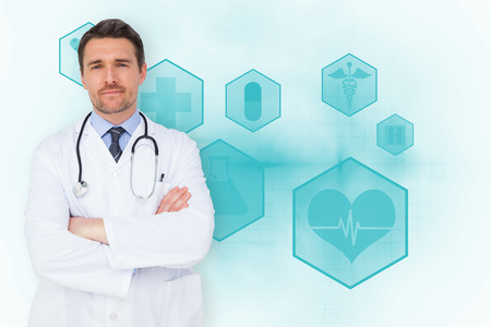 Handsome young doctor with arms crossed against blue medical interface with icons photo