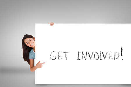 involved: Pretty brunette showing card with get involved against grey background