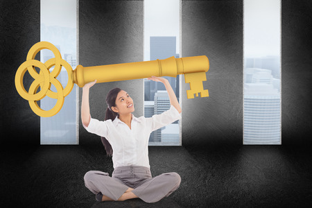 large doors: Businesswoman sitting cross legged carrying large key against graphic with doors and a light bulb on gloomy countryside Stock Photo