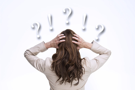 Young classy businesswoman with hands on head standing back to camera against question and exclamation marks Stock Photo