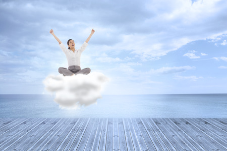 Cheering businesswoman sitting cross legged against beautiful blue sky with clouds photo