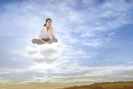 slumped: Businesswoman sitting cross legged thinking against scenic landscape with blue cloudy sky