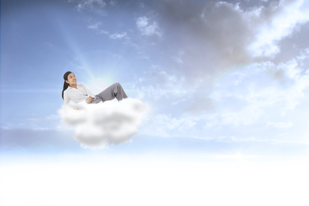 Relaxed businesswoman lying against beautiful blue sky