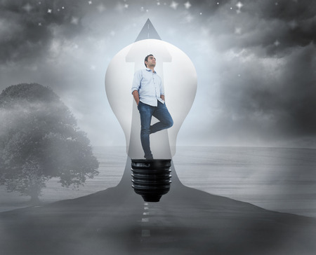 Thinking man in light bulb against road turning into arrow photo