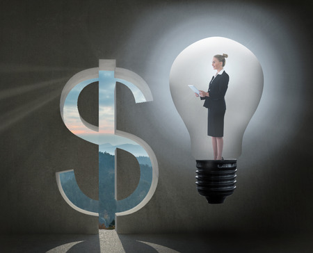 Businesswoman holding tablet in light bulb against dollar sign door  photo