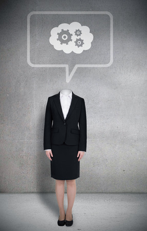 Composite image of headless businesswoman with cogs in speech bubble in grey room photo