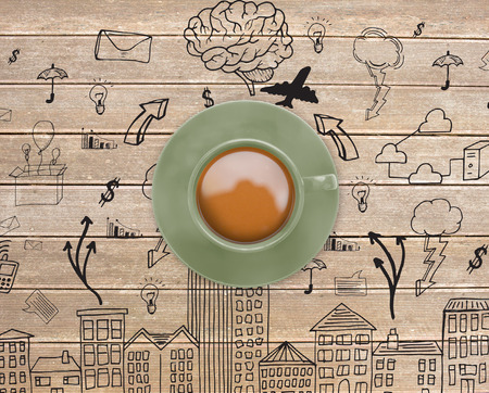 Green cup of coffee against wooden surface with planks and doodle photo