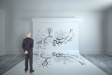 Rear view of mature businessman posing against large white screen showing doodle photo