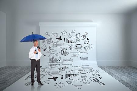 Happy businessman holding umbrella against large white screen showing doodle photo