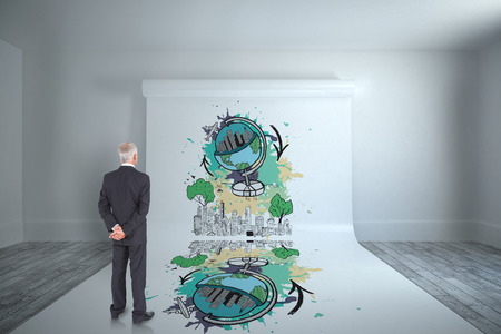 Rear view of mature businessman posing against large white screen showing graphic photo