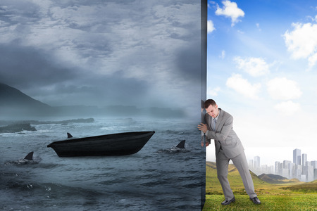 Composite image of businessman pushing away scene of sail boat being circled by sharks photo