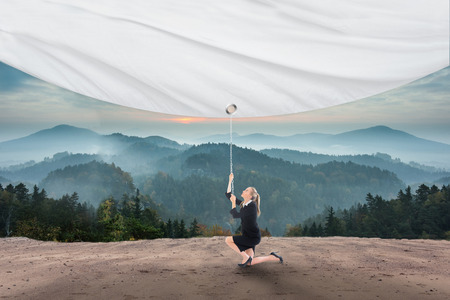 Businesswoman pulling a white screen against scenic countryside with mountains photo