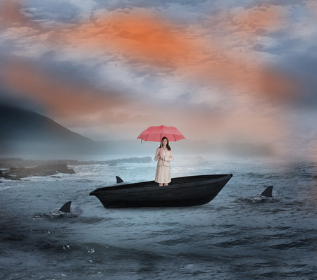 Composite image of attractive businesswoman holding red umbrella in a sailboat being circled by sharks photo