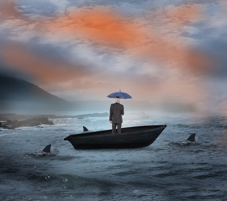 Composite image of businessman holding umbrella in a sailboat being circled by sharks photo