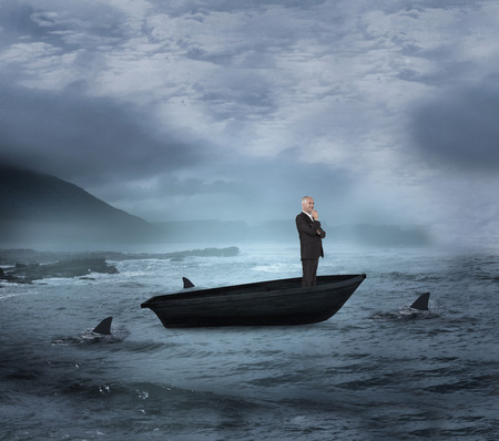 Composite image of happy businessman looking away in a sailboat being circled by sharks photo
