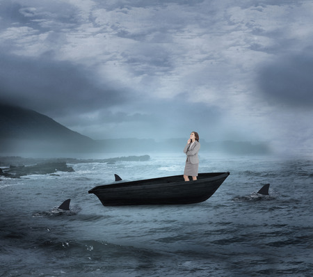 Composite image of smiling thoughtful businesswoman in a sailboat being circled by sharks photo