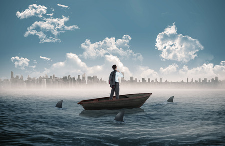 Composite image of businessman holding his jacket against sharks circling a small boat in the sea photo