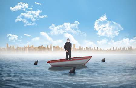 Rear view of mature businessman posing against sharks circling a small boat in the sea photo