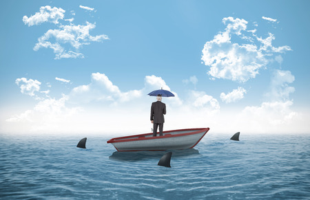 Businessman holding umbrella against sharks circling small boat in the ocean photo
