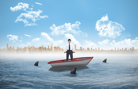 Sad tradesman showing his empty pockets against sharks circling a small boat in the sea photo