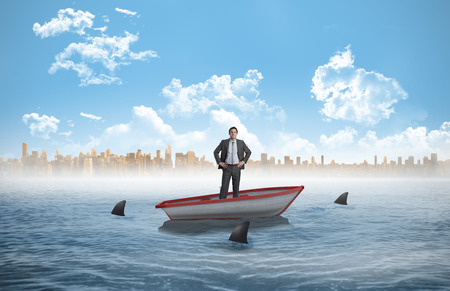 circling: Smiling businessman with hands on hips against sharks circling a small boat in the sea