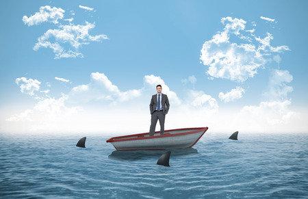 circling: Thinking businessman against sharks circling small boat in the ocean Stock Photo