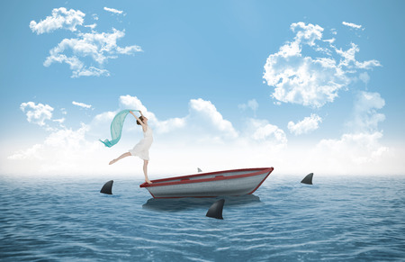 Young beautiful female dancer with blue scarf against sharks circling small boat in the ocean photo