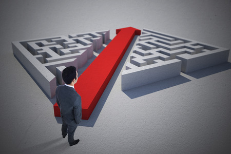 cutting through: Businessman standing against red arrow cutting through puzzle