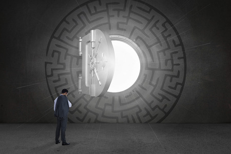 Businessman standing against open safe in middle of maze on black wall photo