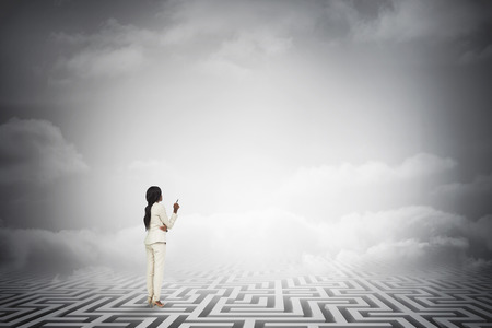 Thinking businesswoman against maze ending in cloudy sky photo