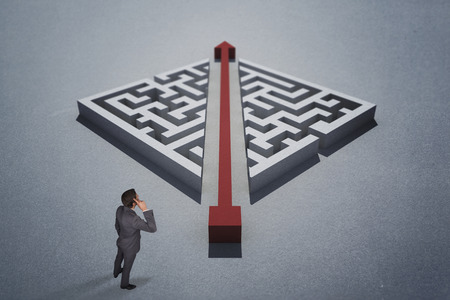 Thinking businessman scratching head against red arrow cutting through puzzle photo